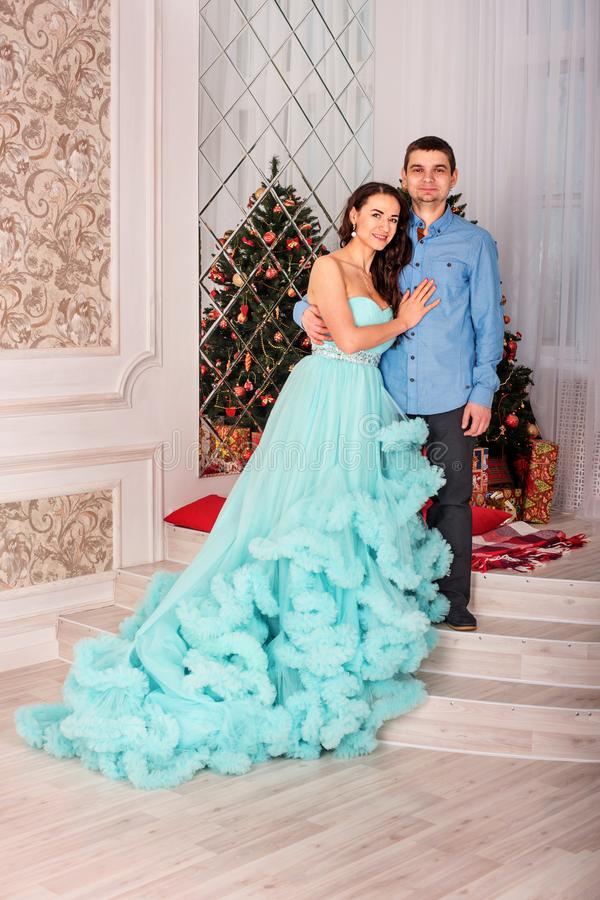 Junge schöne Paare von mittlerem Alter in der eleganten Kleidung und in einem ausgezeichneten Kleid nahe dem Baum des neuen Jahre stockbilder