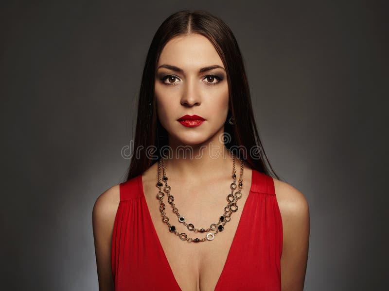 Junge schöne reizvolle Frau Tragender Schmuck des Schönheitsmädchens Elegante Dame im roten Kleid lizenzfreie stockfotos