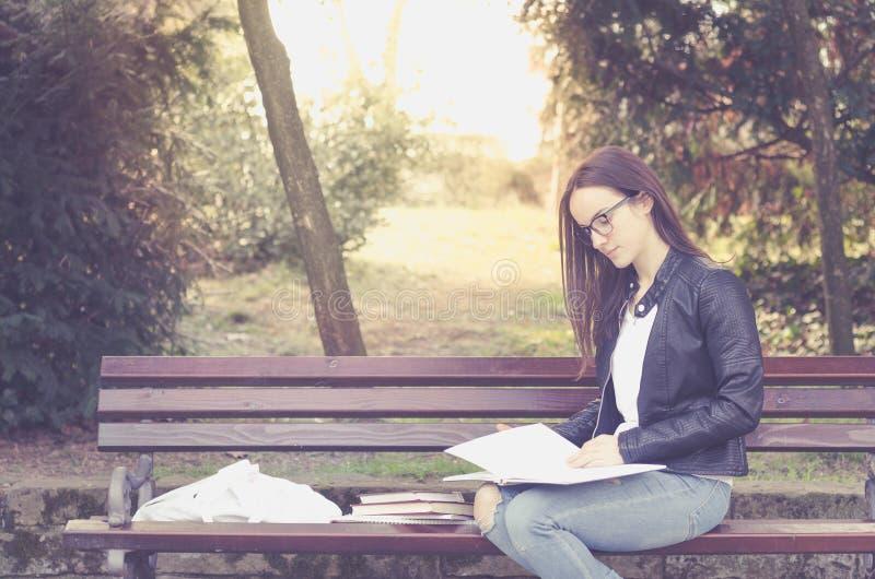Junge schöne Schule oder Studentin mit den Brillen, die auf der Bank im Park die Bücher und die Studie für Prüfung, educ lesend s lizenzfreie stockfotografie