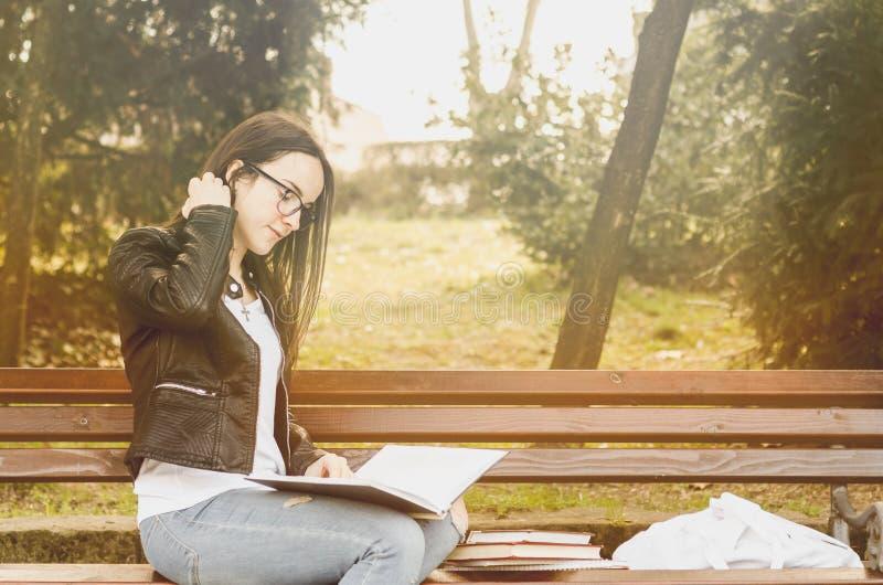 Junge schöne Schule oder Studentin mit den Gläsern, die auf der Bank im Park die Bücher und die Studie für Prüfung lesend sitzen stockfotos