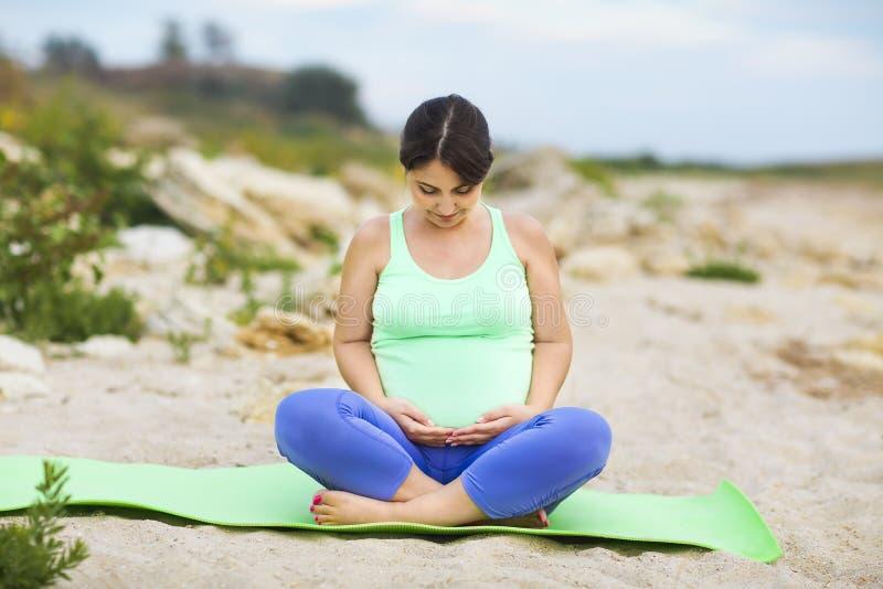 Junge schöne schwangere Frau, die Übungen auf dem Strand tut stockbilder
