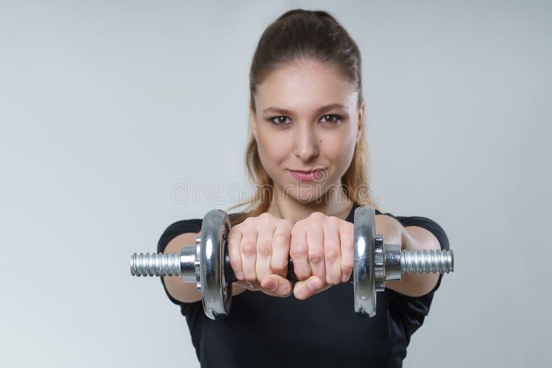 Junge schöne sexy Frau mit dem Brunettehaar in einem schwarzen T-Shirt mit Metalldummköpfen, Porträteignungs-Sportfoto lizenzfreies stockbild