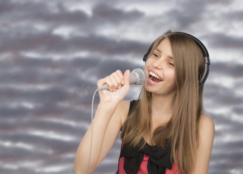Junge schöne singende Jugendliche stockfoto