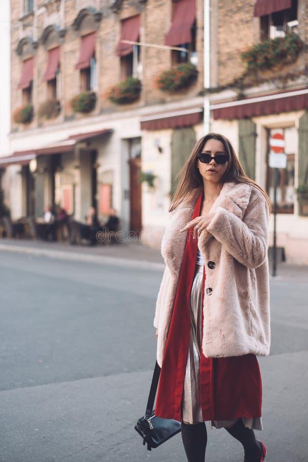 Junge schöne stilvolle Frau, die in rosa Mantel geht stockfoto