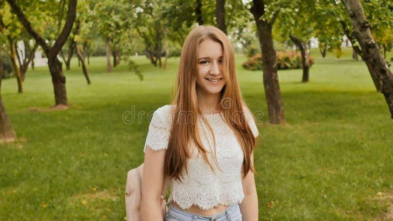 Junge schöne Studentin mit dem langen Haar mit einem Rucksack auf ihr zurück geht in den Park Rest während der Studie lizenzfreie stockfotografie