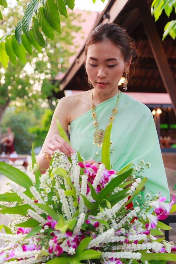 Junge schöne thailändische Asiatinbehandlung im Retro- traditionellen thailändischen Kostüm der Weinlese, das Blumenvase vereinba stockbilder