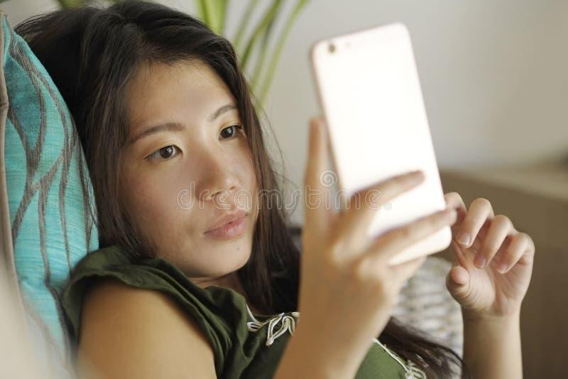 Junge schöne und entspannte asiatische Chinesin, die zu Hause Wohnzimmersofacouch unter Verwendung des Internets auf dem Handy gl lizenzfreie stockfotografie