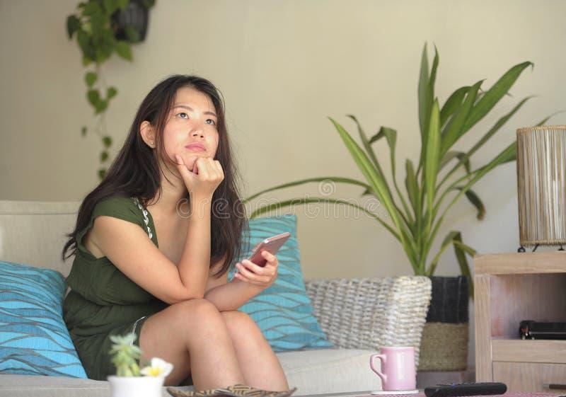 Junge schöne und entspannte asiatische Chinesin, die zu Hause Wohnzimmersofacouch unter Verwendung des Internets auf dem Handy gl lizenzfreies stockbild