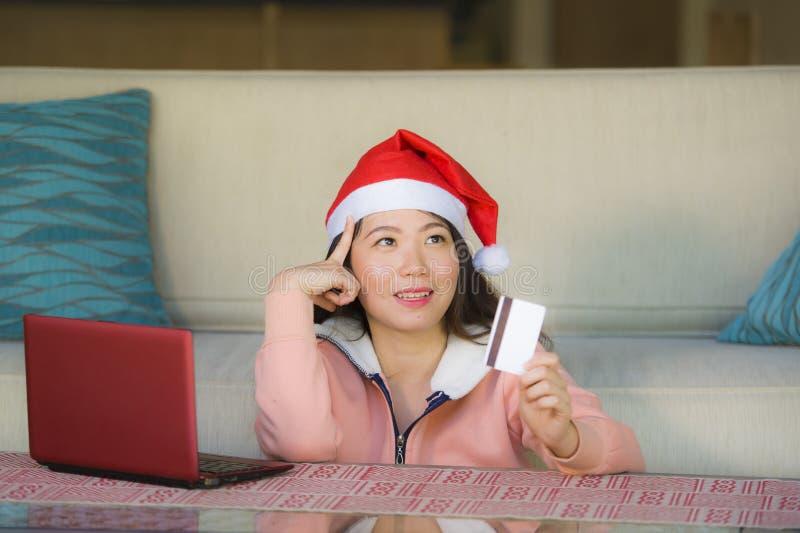 Junge schöne und glückliche asiatische Chinesin, die Sankt-Hutholdingkreditkarte und Weihnachtspräsentkarton unter Verwendung der lizenzfreies stockbild