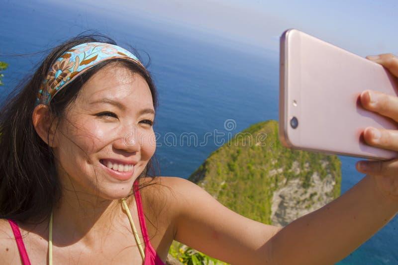 Junge schöne und glückliche asiatische koreanische touristische Frau, die selfie Porträt mit Handy in der Strandseeklippenlandsch stockfoto