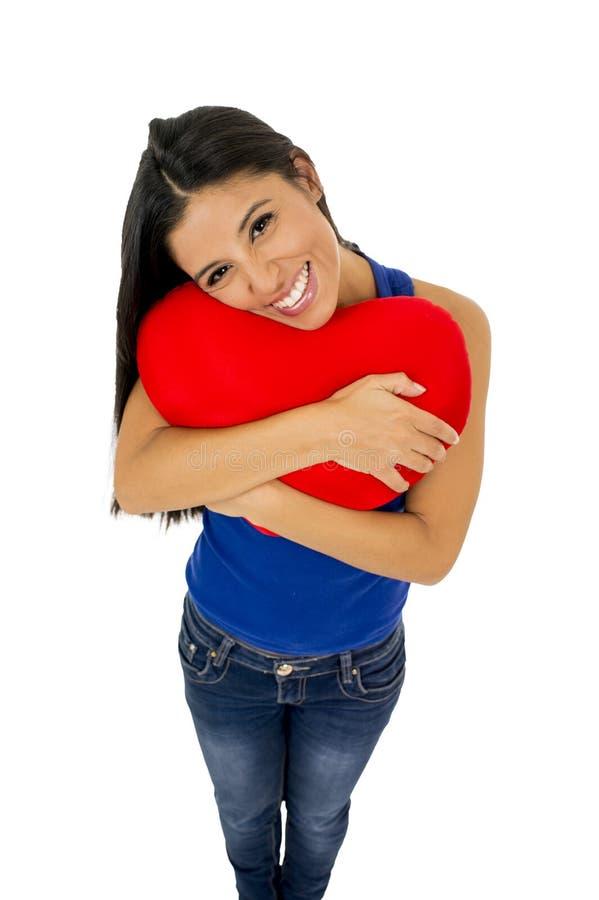 Junge schöne und glückliche Frau, die das rote Kissenherz-Formlächeln lokalisiert im Weiß hält stockfotografie