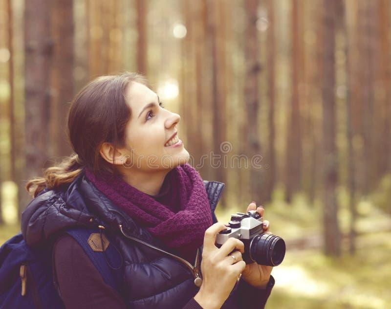 Junge, schöne und glückliche Frau, die in Wald geht und PU nimmt stockbild