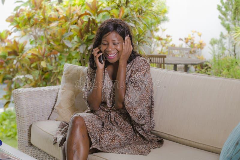 Junge schöne und glückliche Schwarzafrikaner Amerikanerin, die auf nettem und entspanntem Sitzen des Handys an der Sofacouch im H stockfotografie