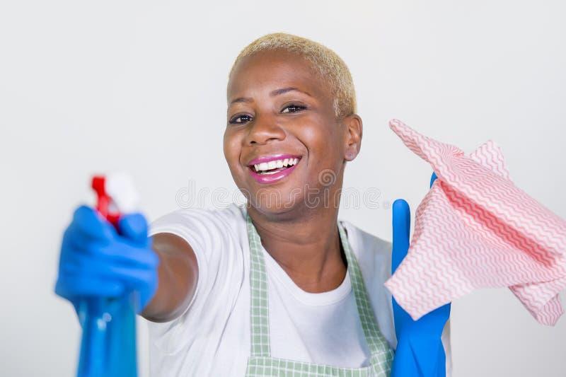 Junge schöne und glückliche schwarze afroe-amerikanisch Frau, die reinigende Sprühflasche als lächelnde spielerische Reinigung de stockbild