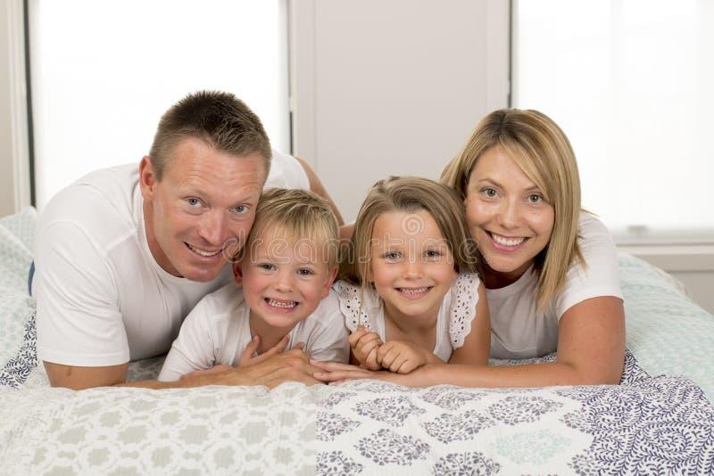 Junge schöne und leuchtende alte lächelnde glückliche aufwerfende süße Lügen der Paare 30 bis 40 Jahre auf Bett mit kleinem Sohn  lizenzfreie stockfotografie