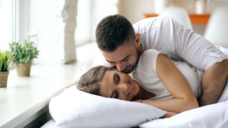 Junge schöne und liebevolle Paare wachen am Morgen auf Attraktiver Mannkuß und umarmen seine Frau im Bett lizenzfreies stockfoto