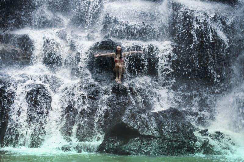 Junge schöne und süße Asiatin im Bikini, der Körper nassen Unterstrom des natürlichen erstaunlichen Wasserfalls sitzt auf Felseng stockbild