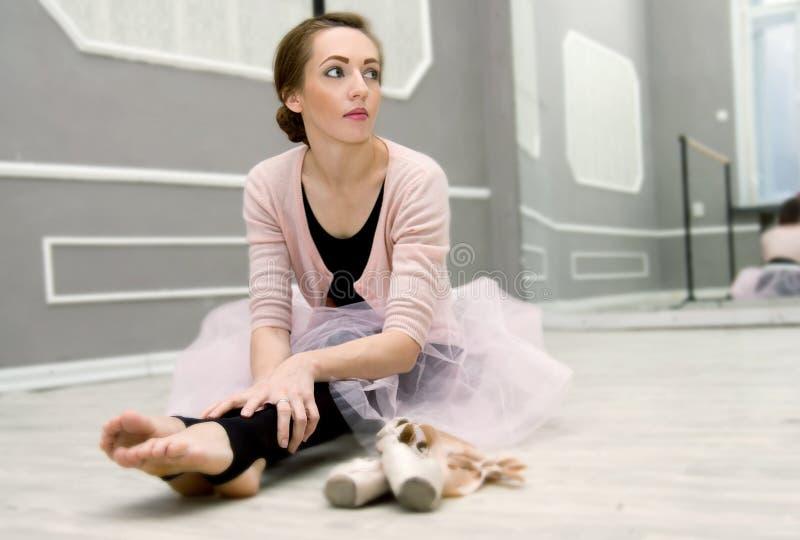 Junge schöne würdevolle Ballerina, die in Ballettklasse sitti stillsteht stockfotografie