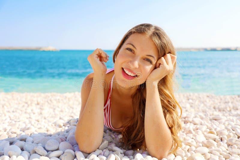 Junge Schönheit auf dem Strand, der Kamera mit dem Horizont im Hintergrund betrachtet lizenzfreies stockbild