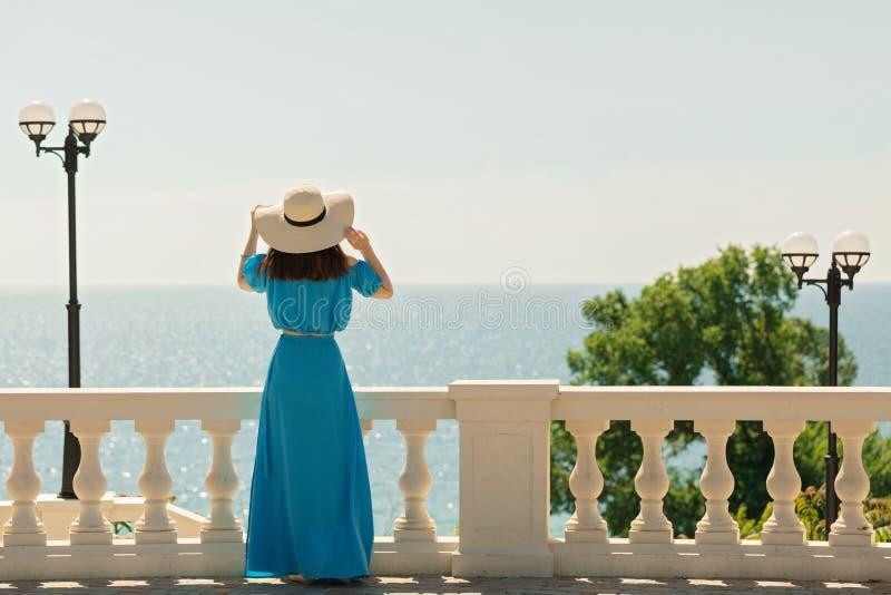 Junge Schönheit auf der Promenade auf dem Meer in azurblauem langem stockfotografie