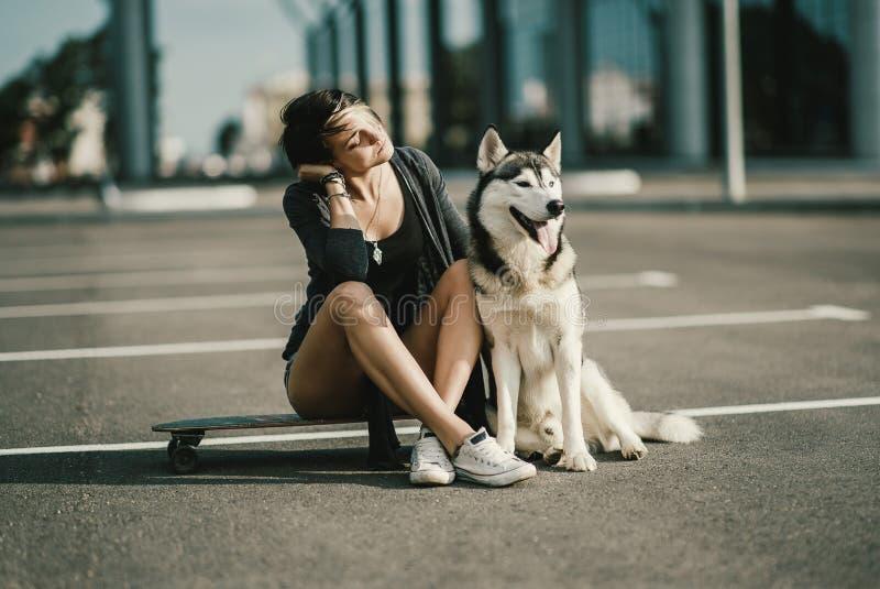 Junge Schönheit auf der Straße, die ihren heiseren Hund sitzt auf einem Skateboard oder einem longboard umarmt lizenzfreie stockfotos