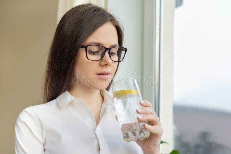 Junge Schönheit in den Gläsern mit Glas Mineralwasser mit Zitrone, Geschäftsfrauen auf Bruch frisches Gesundheitsvitamin trinkend lizenzfreie stockfotos
