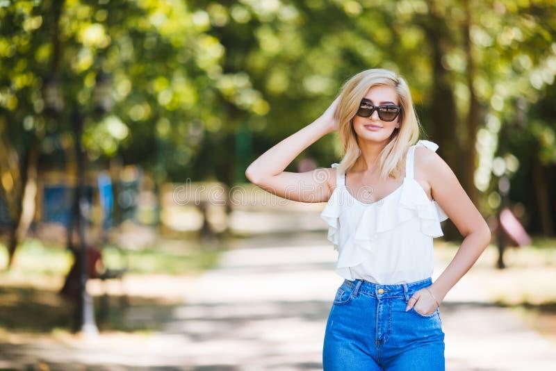 Junge Schönheit in der Sonnenbrille am sonnigen Tag im Park stockfoto