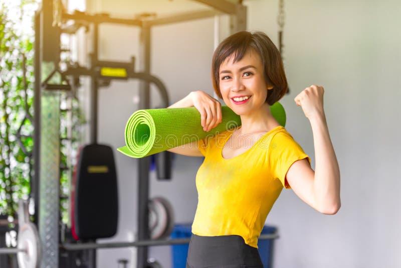 Junge Schönheit in der Sportkleidung Sie ` s, das eine Trainingsmatte hält Gehen, den ausbildenden Sport, Gymnastik zu tun lizenzfreie stockfotografie