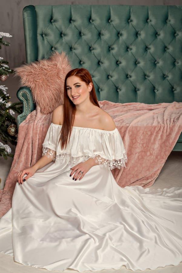Junge Schönheit des Porträts im weißen eleganten Abendkleid, das auf Boden nahe Sofa sitzt lizenzfreies stockfoto