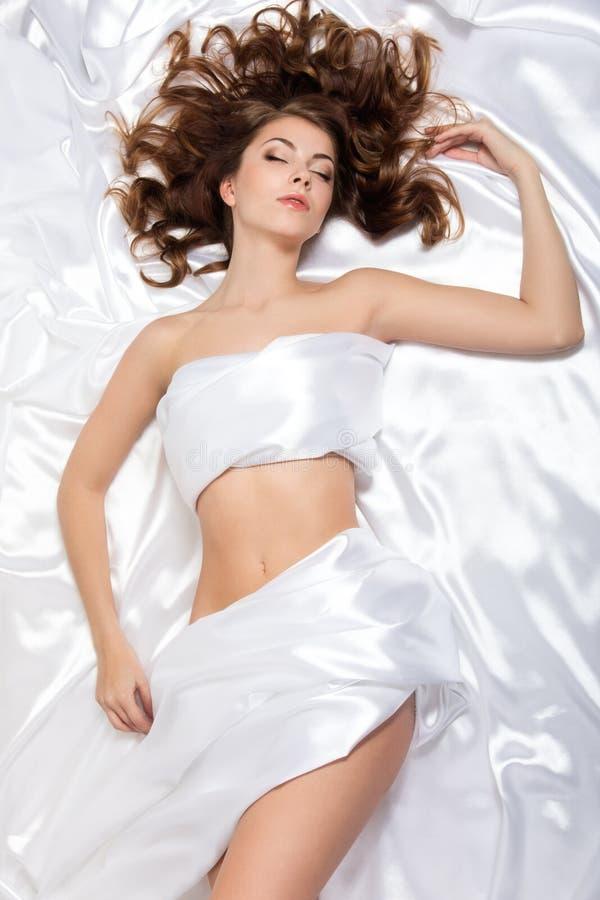 Junge Schönheit, die über weißem silk Hintergrund liegt lizenzfreies stockbild
