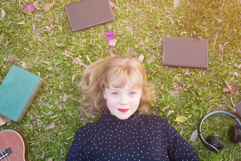 Junge Schönheit, die auf das Gras legt stockfotos