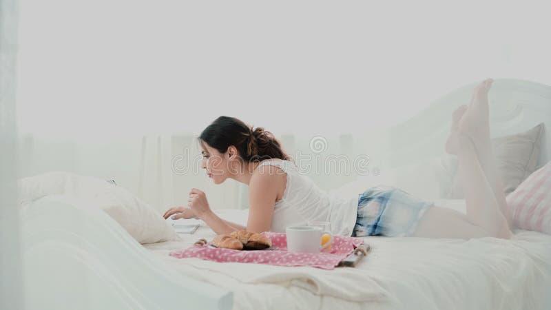 Junge Schönheit, die auf dem Bett liegt und Laptop verwendet Mädchen surft das Internet, am Morgen und ihr Frühstück an zu essen stockfotografie