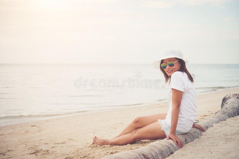 Junge Schönheit, die auf der tragenden Sonnenbrille des Strandes sitzt f lizenzfreies stockfoto