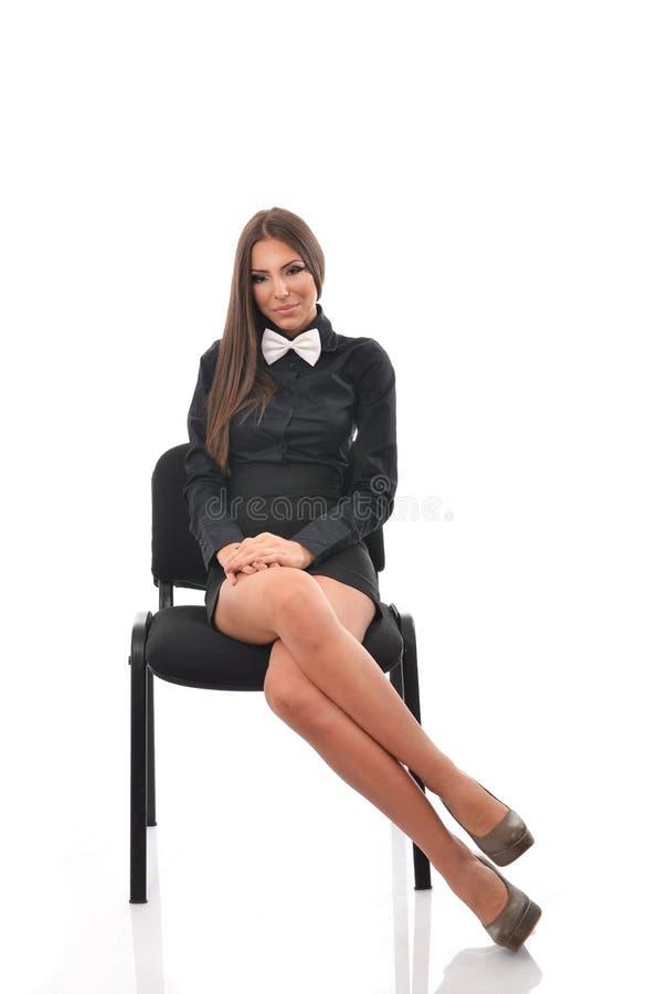Junge Schönheit, die auf einem Stuhl mit ihren Beinen gekreuzt stationiert lizenzfreies stockbild