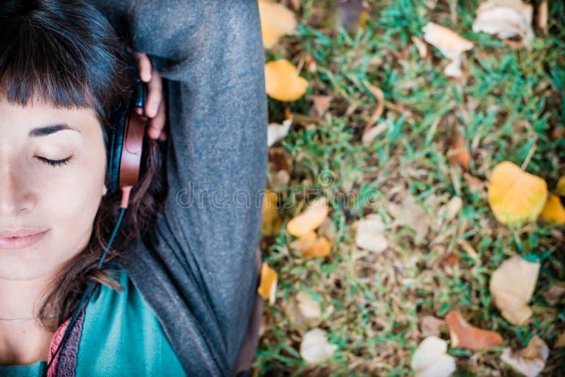 Junge Schönheit, die auf Musikherbst hört lizenzfreie stockfotos