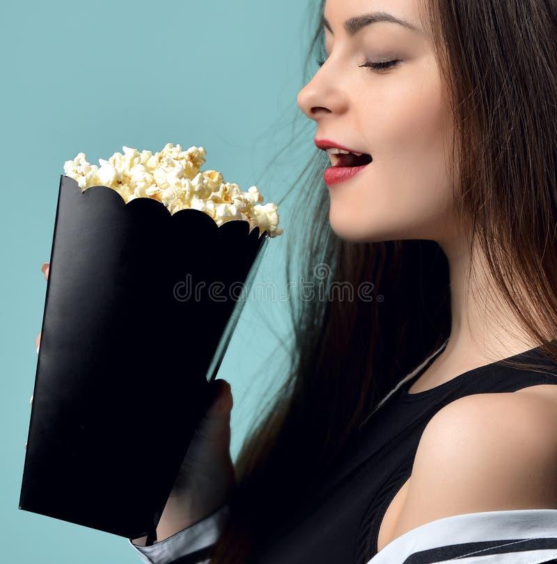 Junge Schönheit, die das Essen des Popcorns über tadellosem backgroun hält stockfoto
