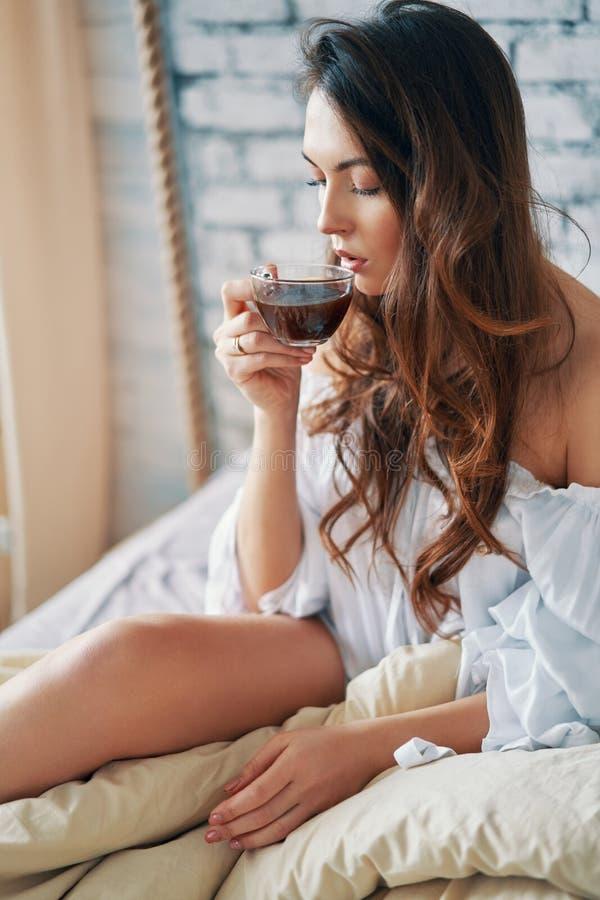 Junge Schönheit, die den heißen Kaffee sitzt im Bett und genießt ihren guten Morgen trinkt lizenzfreie stockfotografie