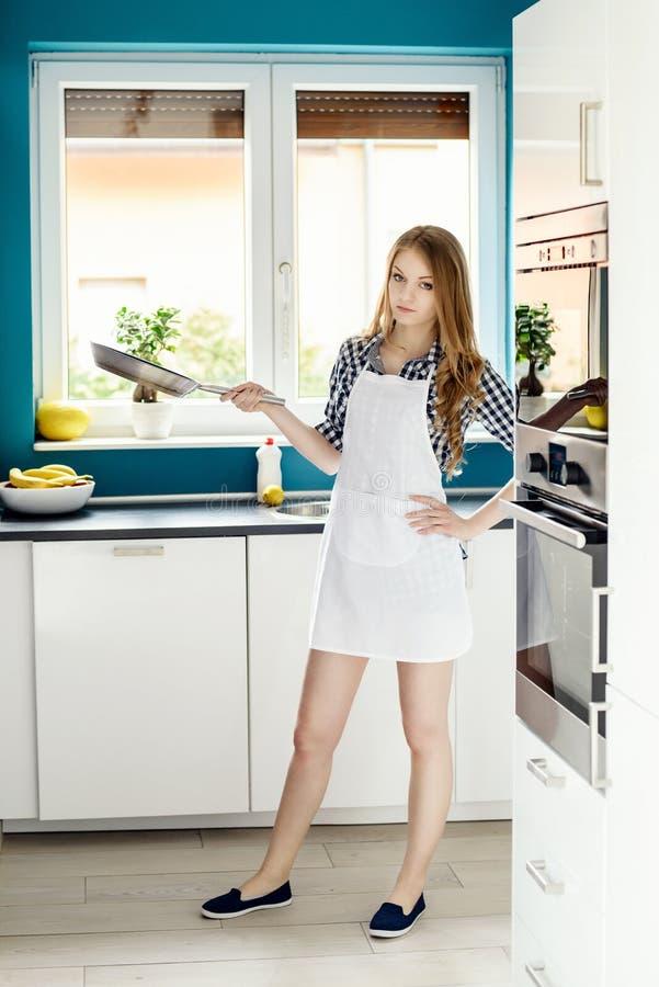 Junge Schönheit, die in der Küche mit einer Bratpfanne aufwirft lizenzfreie stockbilder