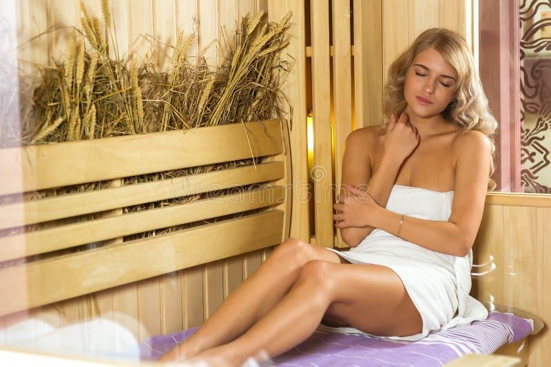 Junge Schönheit, die in der Sauna eingewickelt im Tuch sich entspannt lizenzfreies stockfoto