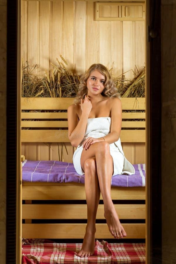 Junge Schönheit, die in der Sauna eingewickelt im Tuch sich entspannt stockfotografie