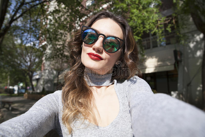 Junge Schönheit, die draußen Selbstporträt selfie nimmt lizenzfreie stockfotografie