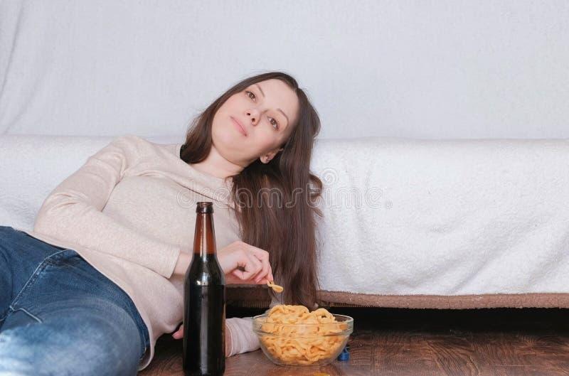 Junge Schönheit, die ein Bier trinkt und die Chips legen auf den Boden nahe der Couch isst Ungefähr lächeln und träumen lizenzfreie stockfotografie