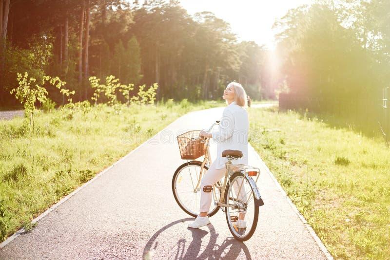 Junge Schönheit, die Fahrrad in einem Park fährt Aktive Leute Entspannen Sie draußen sich lizenzfreies stockfoto