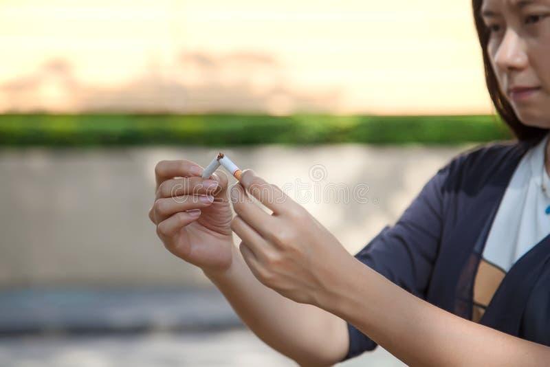 Junge Schönheit, die gebrochene Zigarette hält lizenzfreie stockfotos