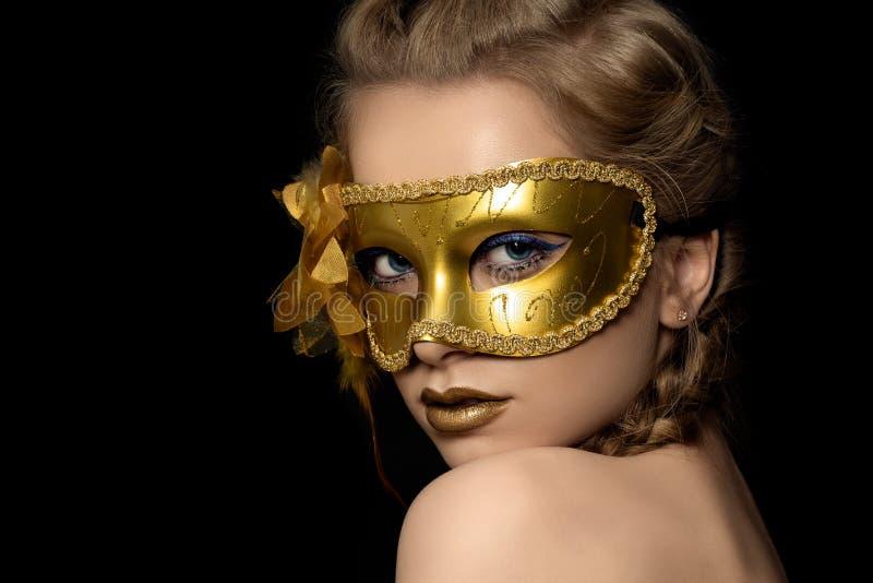 Junge Schönheit, die goldene Parteimaske trägt lizenzfreies stockfoto