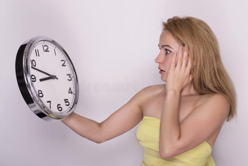 Junge Schönheit, die große Uhr hält Setzen Sie Zeit Konzeptes fest Wenden Sie getrennt auf weißem Hintergrund ein stockbilder