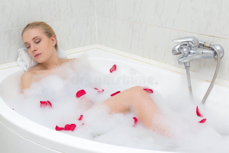 Junge Schönheit, die im Bad mit den roten Blumenblumenblättern sich entspannt stockbild