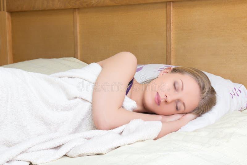 Junge Schönheit, die im Bett schläft lizenzfreies stockbild