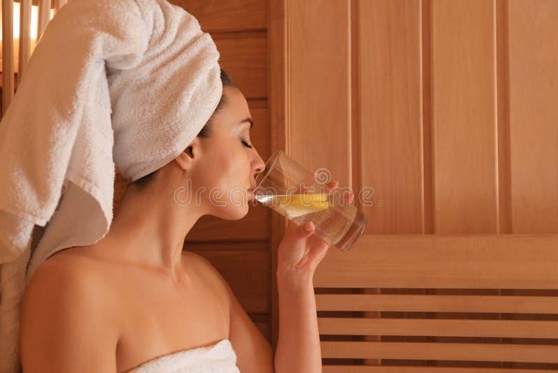 Junge Schönheit, die kaltes Wasser mit Zitrone in der Sauna trinkt lizenzfreies stockfoto