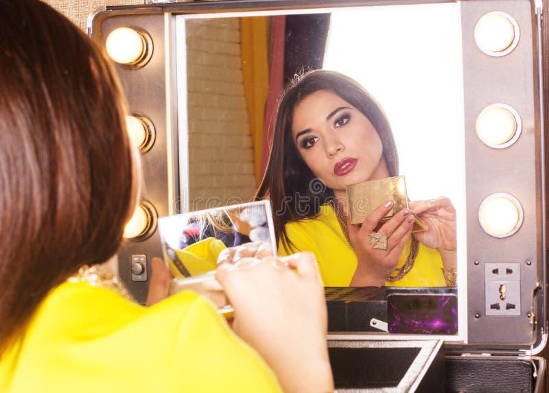 Junge Schönheit, die Make-up nahe Spiegel macht lizenzfreies stockbild